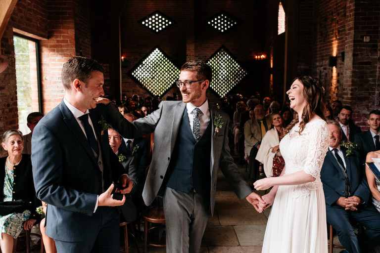 laughing with the best man and the wedding rings