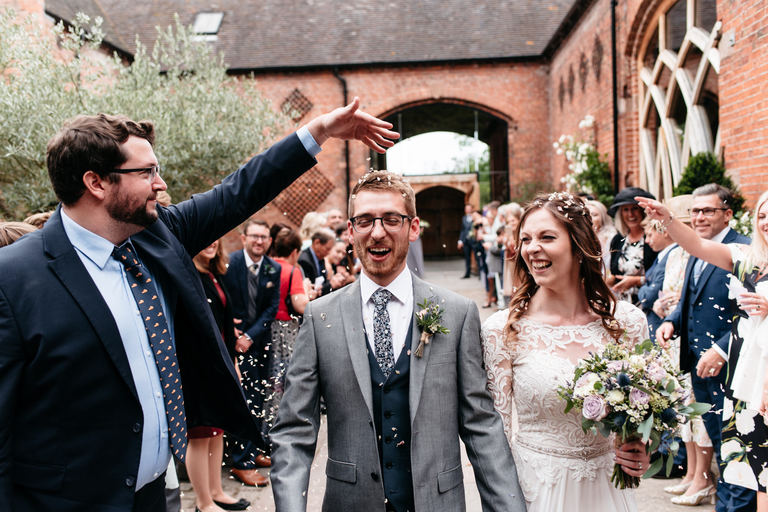 guest dropping confetti on the groom's head