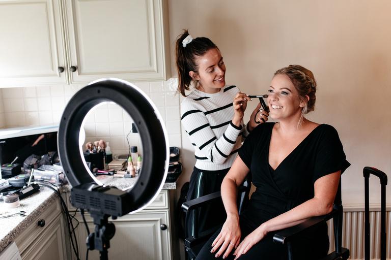 bridesmaid having makeup airbrushed