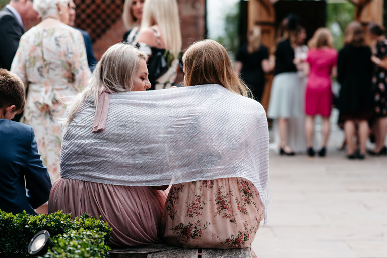 two guests keeping warm under a blanket