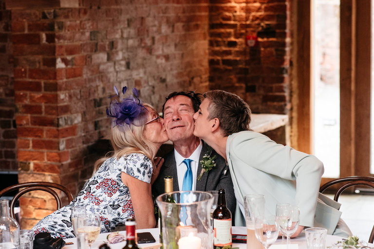 groom's dad receiving two kisses at the same time