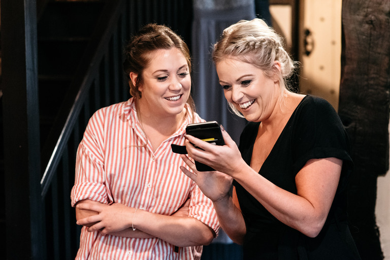two bridesmaids sharing a joke on a phone
