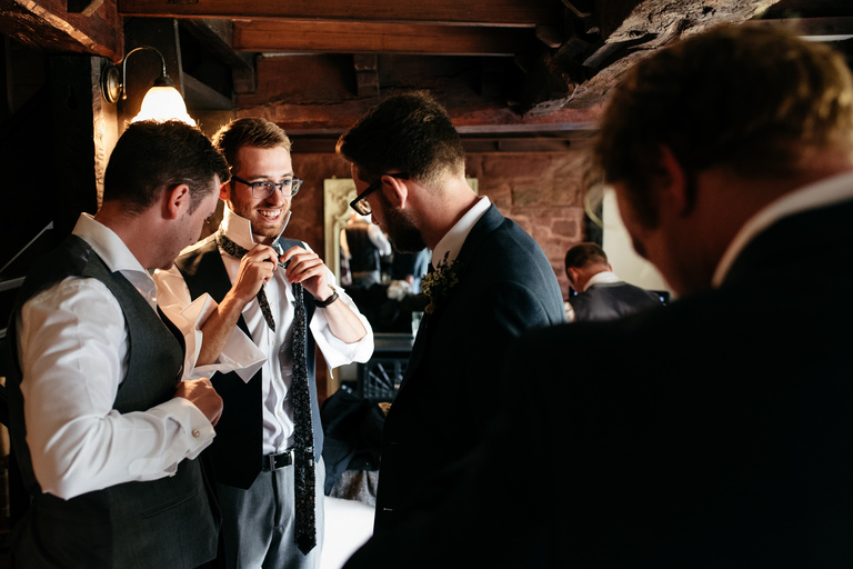 smiling groom trying to fix his tie