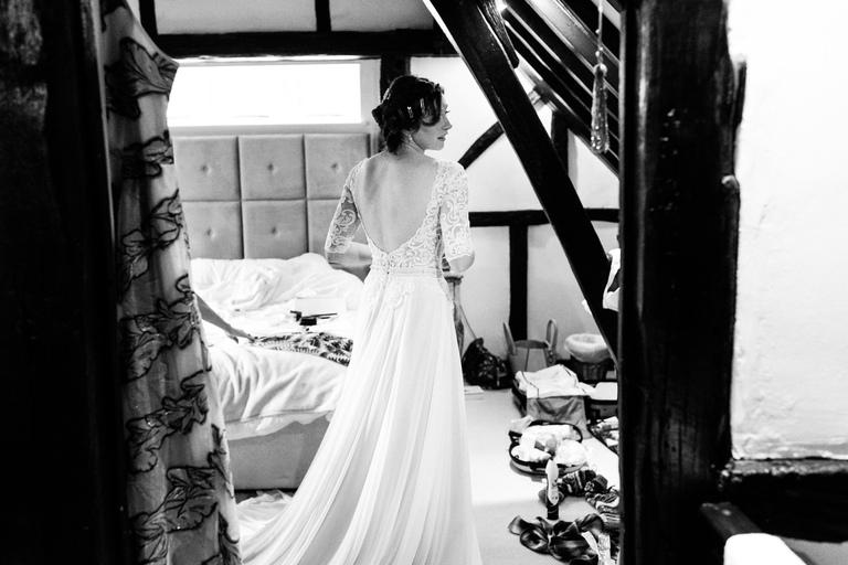 bride admiring her wedding dress in the mirror