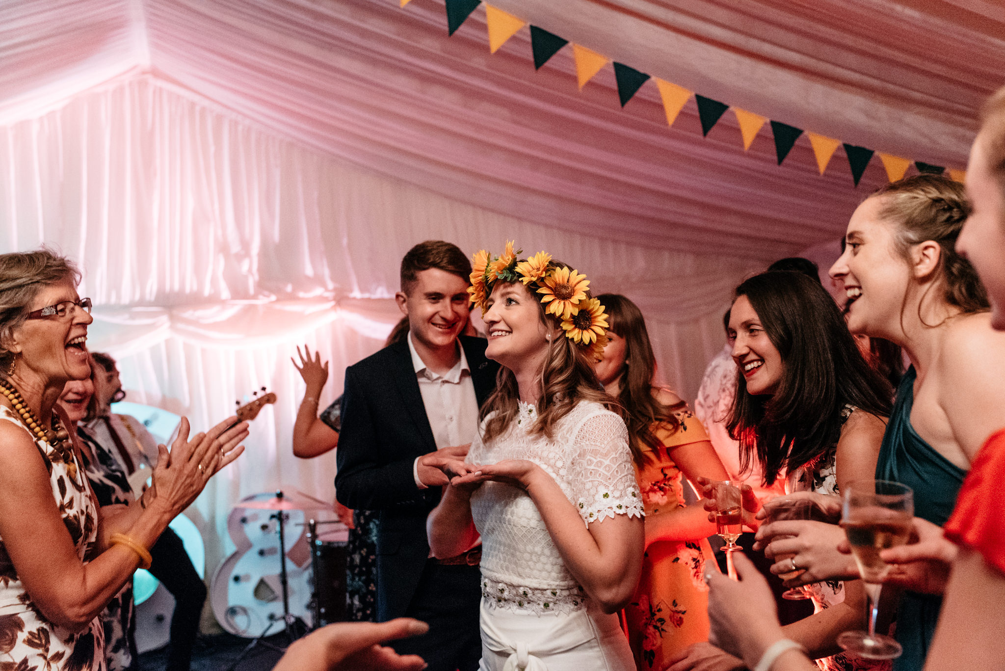 bride surrounded by friends on the dance floor