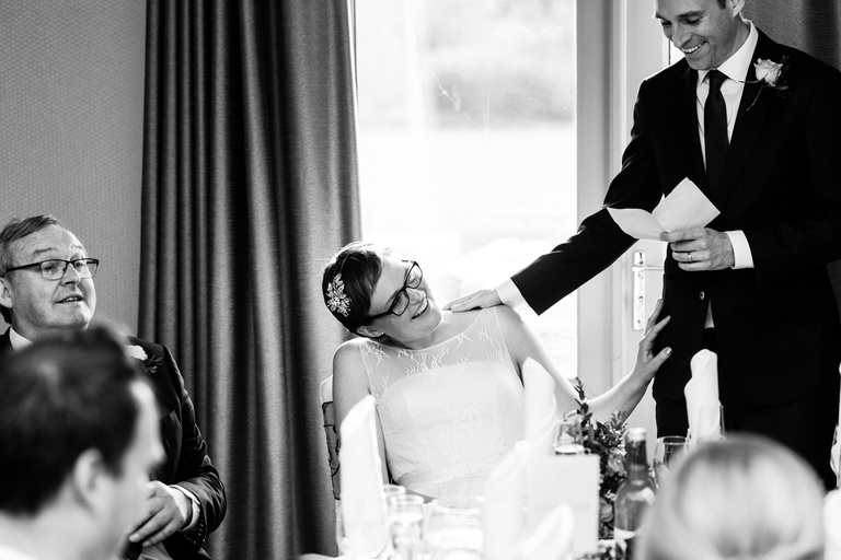 groom places his hand on bride's shoulder during speech