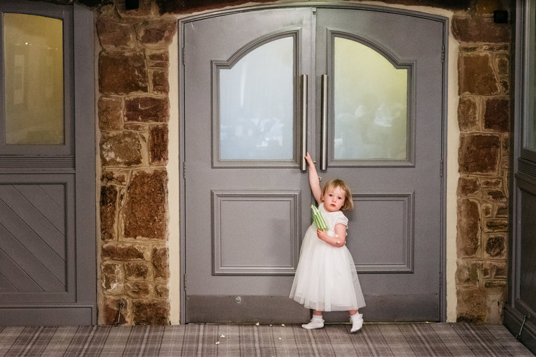 little girl with popcorn opening a door