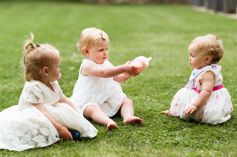 three babies sharing a bottle