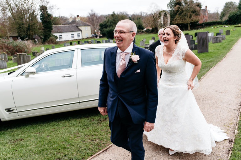 bride with her dad laughing as they arrive at church