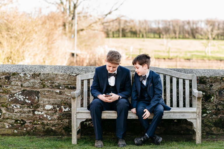 two boys chatting together on a bench