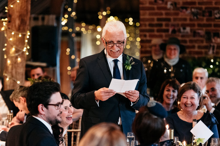proud father of the bride giving his speech smiling