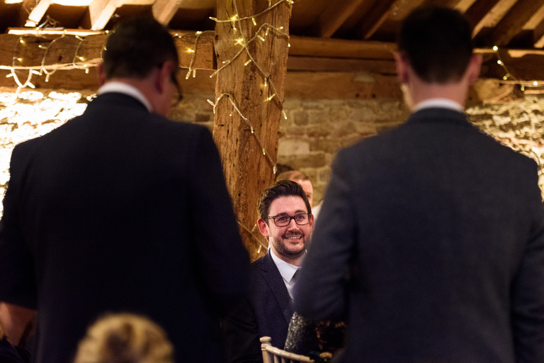 groom watching his brothers give a speech
