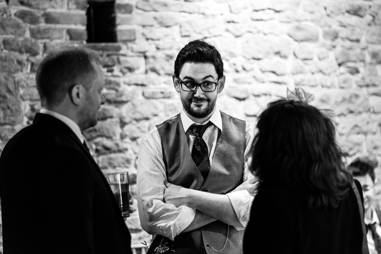 groom with surprised expression chatting to guests