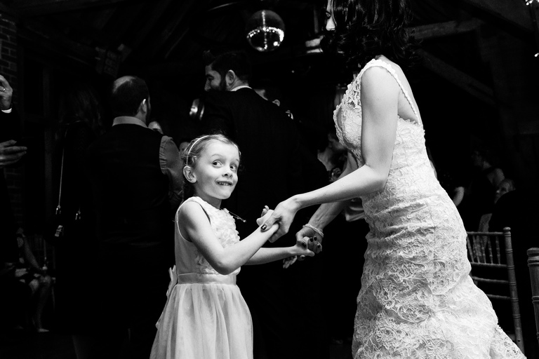 little girl with a great expression dancing with the bride