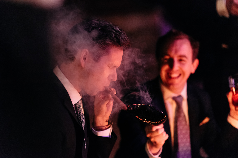 guest lighting a cigar from a burning log