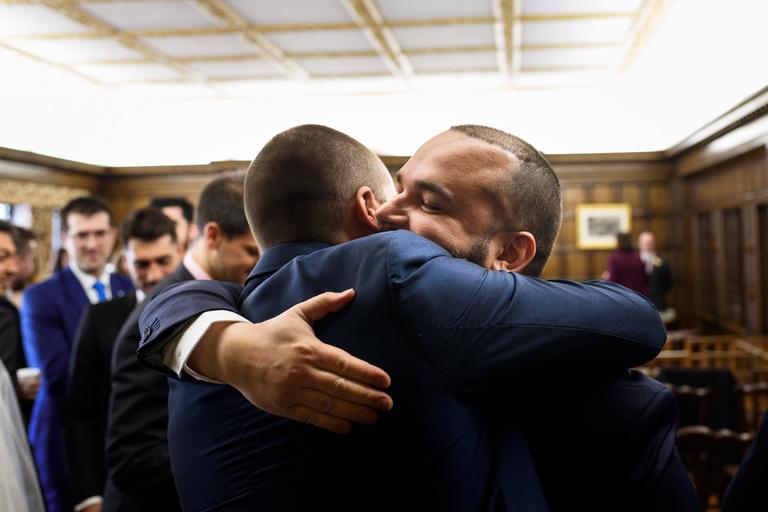 groom hugging friend after wedding