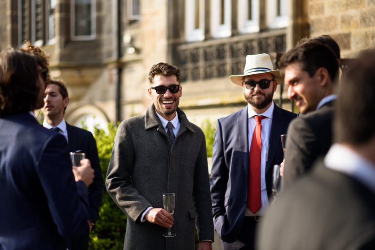 wedding guests in coats and sunglasses