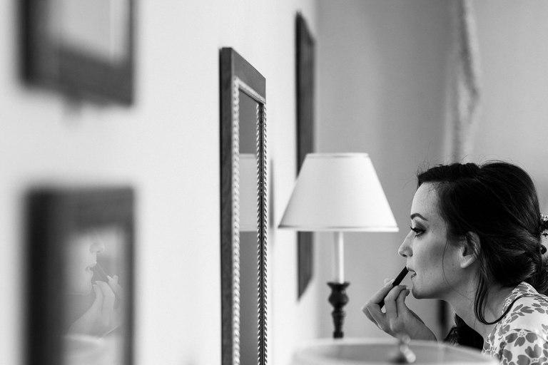 bride putting on lipstick in hotel bedroom mirror