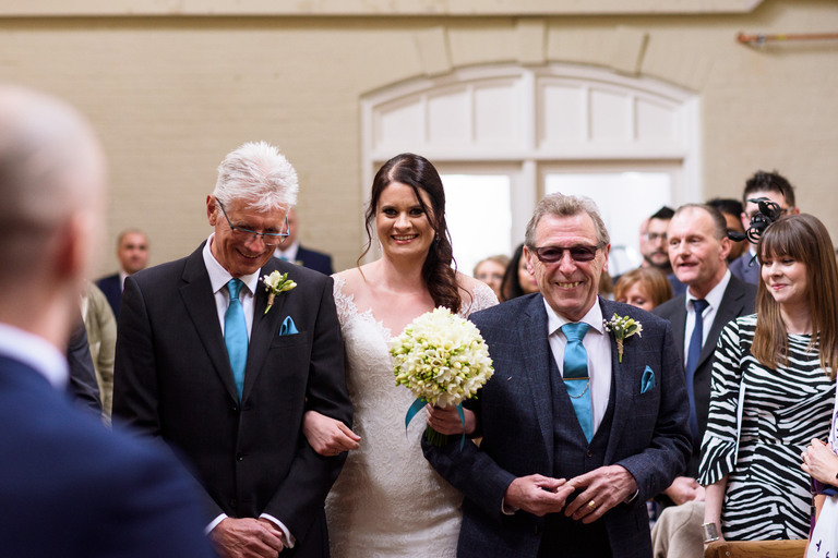 bride walking down the aisle with two dads