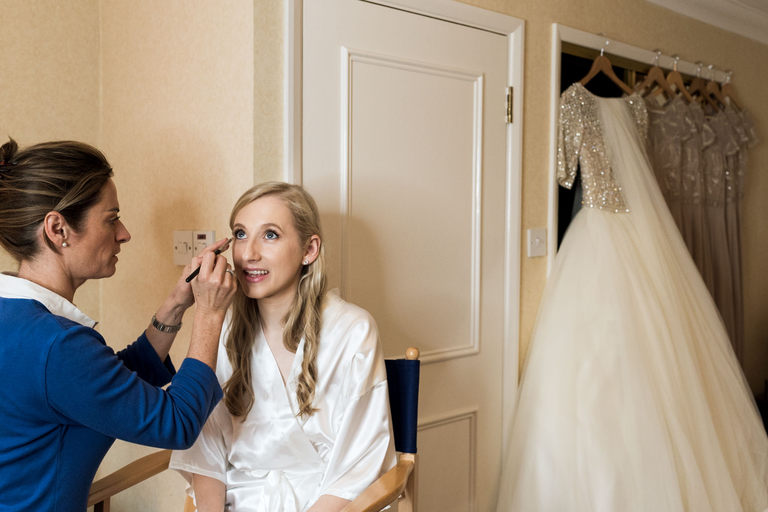 bride in white gown having makeup done