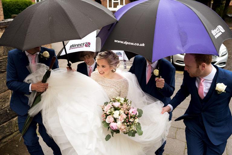 bride arriving underneath umbrellas