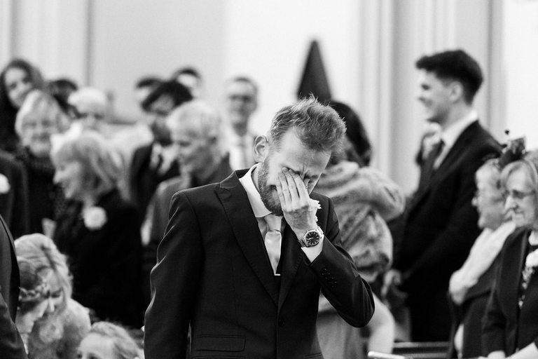 emotional groom wiping away tears