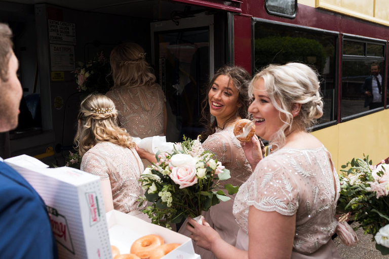 bridesmaids getting on board the wedding bus