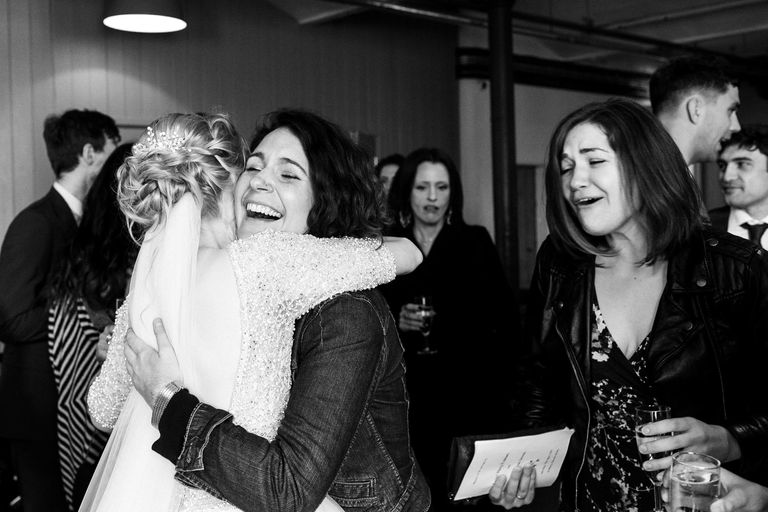 overjoyed friends hugging the bride