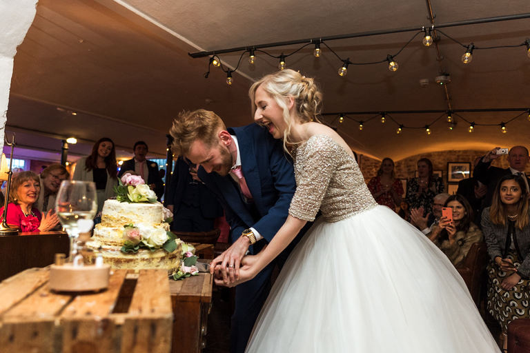 newlyweds cutting the cake at the westmill