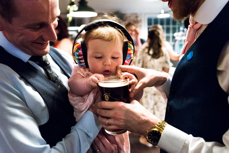 baby wearing headphones trying to drink a pint of beer