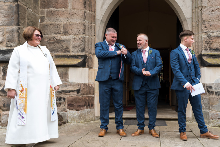 best man and ushers waiting outside the church with vicar