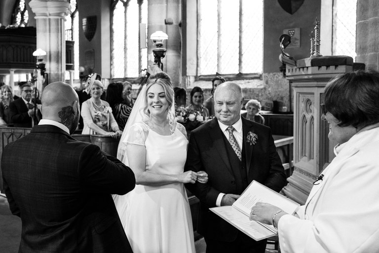 smiling bride arriving at the altar with her dad