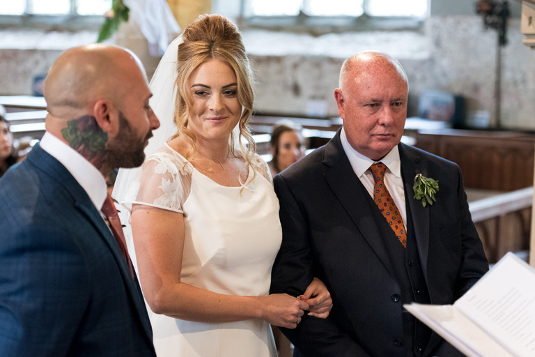 bride giving her groom a cheeky look at the altar