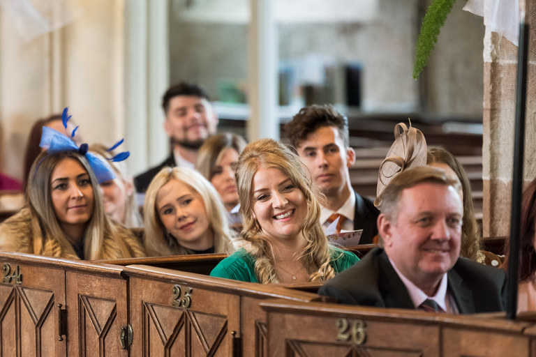 smiling guests looking on from the church pews