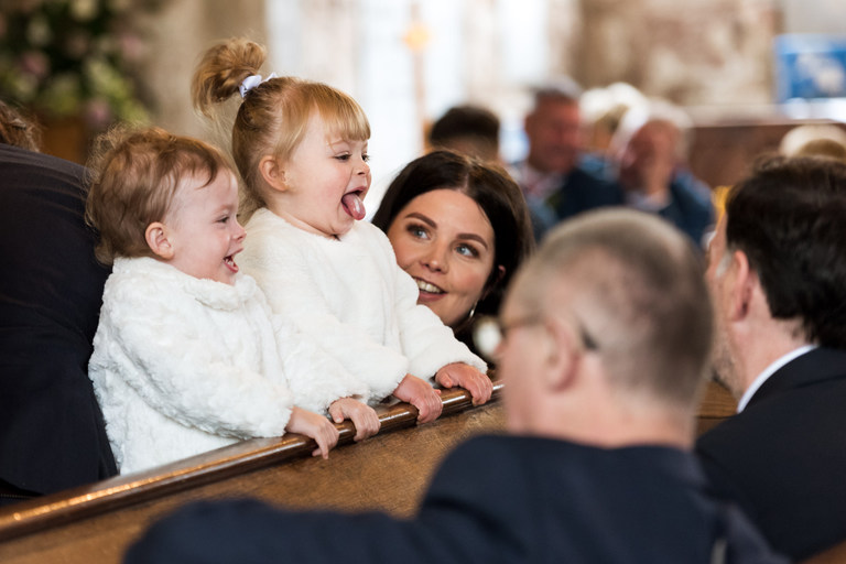 two little girls pulling faces during wedding ceremony