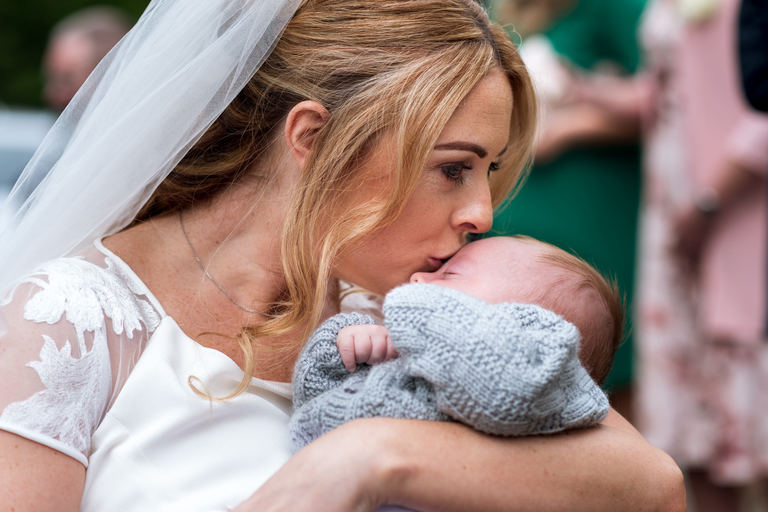 bride kissing her young child