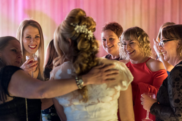 bride's friends admiring her dress