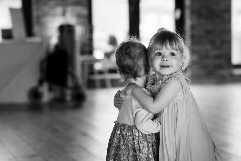 two toddlers hugging on the dance floor