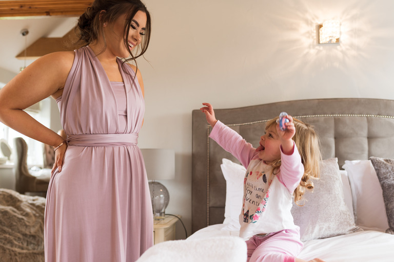 couple's daughter playing with a bridesmaid