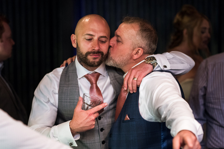 groom receiving a kiss on the cheek from his best mate