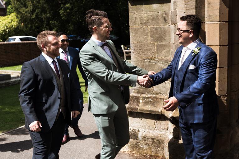 groom greeting friends outside church