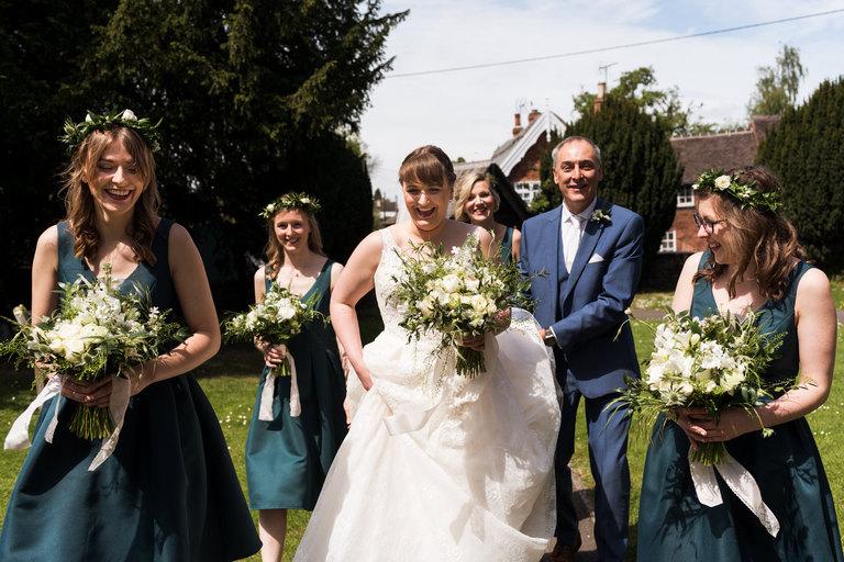 bride walking with dad and bridesmaids