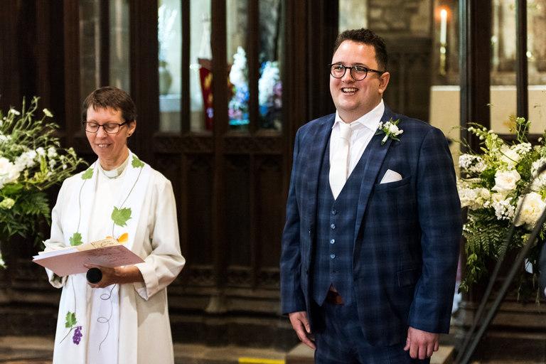 happy groom watching his bride walk down the aisle