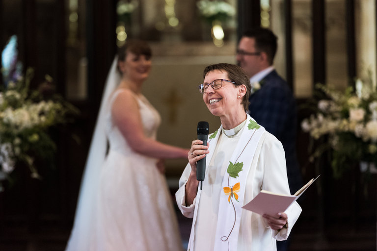 female vicar smiling and talking to the wedding guests