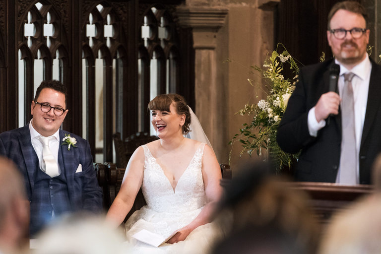 newlyweds laughing during a speech from their pastor