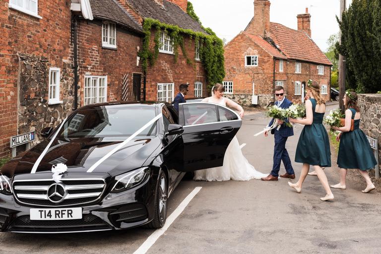 bride getting into the wedding car