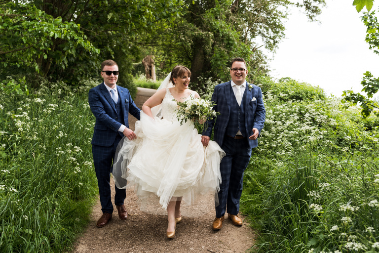 bride and groom going for a walk with usher holding her dress