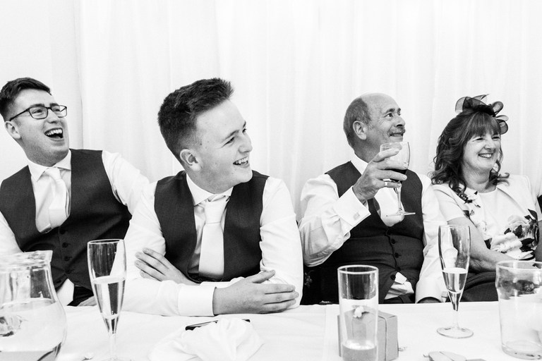 groom's brother and his dad laughing at his speech