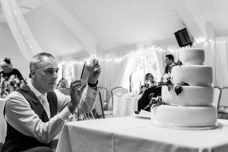 father of the bride taking a photo of the cake