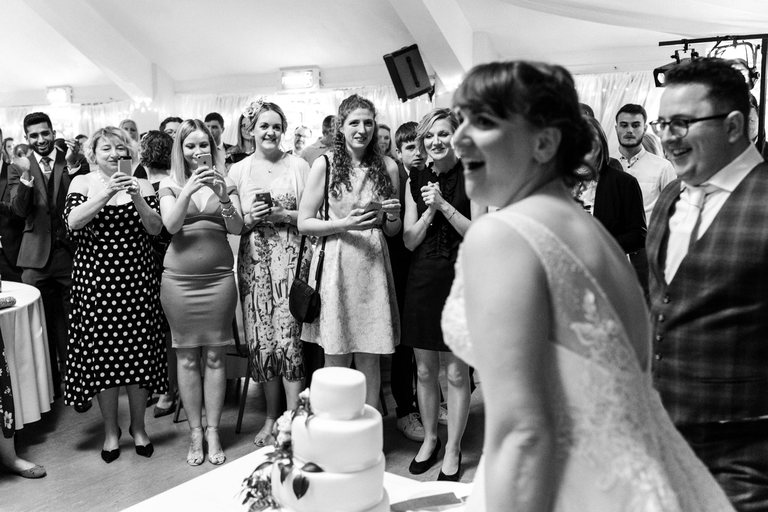 guests watching the happy couple cut the wedding cake